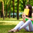 Woman cover the face with book at park - Stock Photo