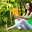 Woman reading book at green park - Stock Photo