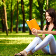Woman reading book and smiling — Stock Photo #7614204