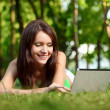 Happy woman laying on grass with laptop — Stock Photo #7614237