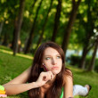 Woman laying on grass and thinking — Stock Photo