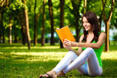 Woman reading book and smiling — Stock Photo