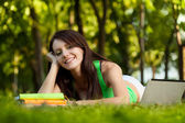 Smiling brunette woman laying on grass — Stock Photo