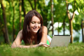 Happy woman laying on grass with laptop — Stock Photo