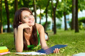 Woman laying on grass and dreaming — Stock Photo