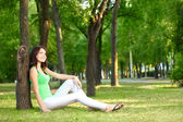 Brunette woman sitting under the tree — Stock Photo