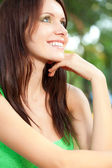 Happy woman sitting under the tree closeup face — Stock Photo