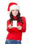 Woman wearing santa hat holding mug on plate — Stock Photo