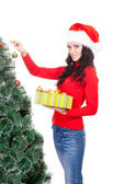 Woman decorating artifical fur tree — Stock Photo