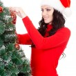 Stock Photo: Happy womdecorating artifical fur tree
