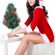 Sexy woman wearing santa helper costume sitting on the sofa - Foto Stock