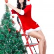 Sexy woman decorating the fur tree on stepladder - Foto Stock
