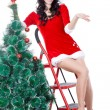 kadın Noel Baba Yardımcısı bir merdiven üzerinde kürk ağacı süsleme — Stok fotoğraf
