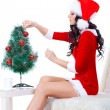 Woman wearing santa helper costume sitting on the sofa - Photo