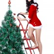 Girl wearing santa costume decorating the fur tree — Stock Photo