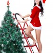 Woman in santa costume standing on stapladder — Stockfoto