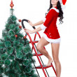 Woman in santa costume standing on stapladder — Stock Photo
