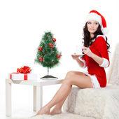 Brunette sitting on the sofa and holding mug — Stock fotografie