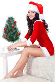 Sexy woman wearing santa helper costume sitting on the sofa — Stock fotografie