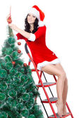 Sexy woman decorating the fur tree on stepladder — Stock Photo
