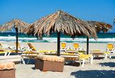 şemsiye ile mavi gökyüzünün altında plajda şezlonglar — Stok fotoğraf