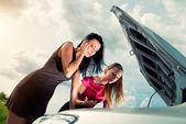 Two young women with broken car on a road — Stock Photo