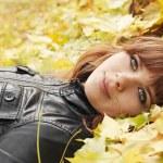 Girl on maple leaves — Stock Photo