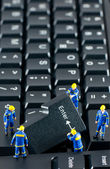Team of construction workers working on a computer keyboard — Stock Photo