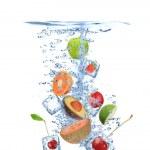 Ice cubes with fruit splashing — Stock Photo