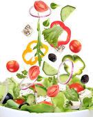 Fresh salad with ingredients in motion — Stock Photo
