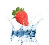 Strawberry dropped into water splash on white — Stock Photo
