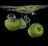 Fresh green apples splashing into the water — Stock Photo