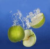 Apple splashing into water — Stock Photo