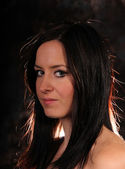 Fashion brunet girl posing on dark background — Stock Photo