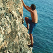 Man climbing the sea rock — Stock Photo