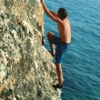 Man climbing the sea rock - Photo