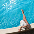 Young woman sitting on the ledge of the pool. — Foto de Stock