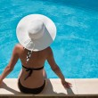 Stockfoto: Young woman sitting on the ledge of the pool.