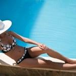 mujer joven sentada en el borde de la piscina — Foto de Stock