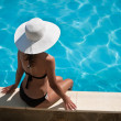 Young womsitting on ledge of pool. — Stock Photo #7534179