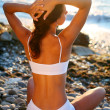 Beautiful brunette sunbathing on the beach — Stock Photo #7539517