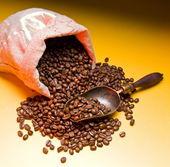 Pytel kávová zrna a lopatka. na pozadí tmavě žluté. — Stock fotografie