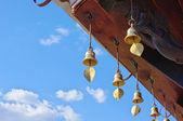 青銅色の鐘が鳴る仏教寺院の屋根の下で風に — ストック写真