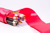 Lápices multicolores con cinta roja — Foto de Stock