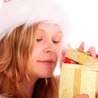 Miss Santa is Sneaking a Peek at a Golden Gift Box — Stock Photo #7854414