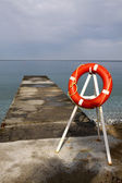 Pier and lifebuoy — Stock Photo