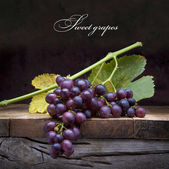 Art purple grapes on old wooden background — Stock Photo