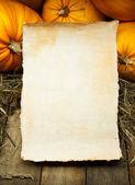 Arte naranja calabazas y hoja de papel sobre fondo de madera — Foto de Stock