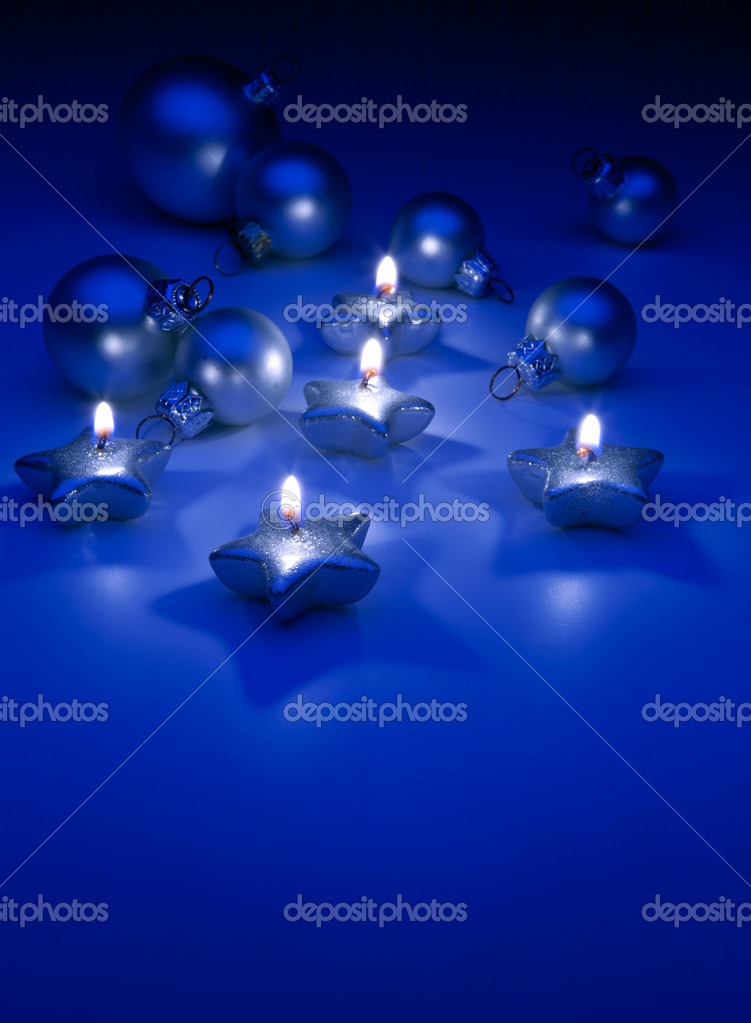 Burning Christmas candles and ornaments on a blue background — Stock Photo #7004437