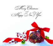 Red Christmas ball with ribbon and bow on white snow — Stock Photo